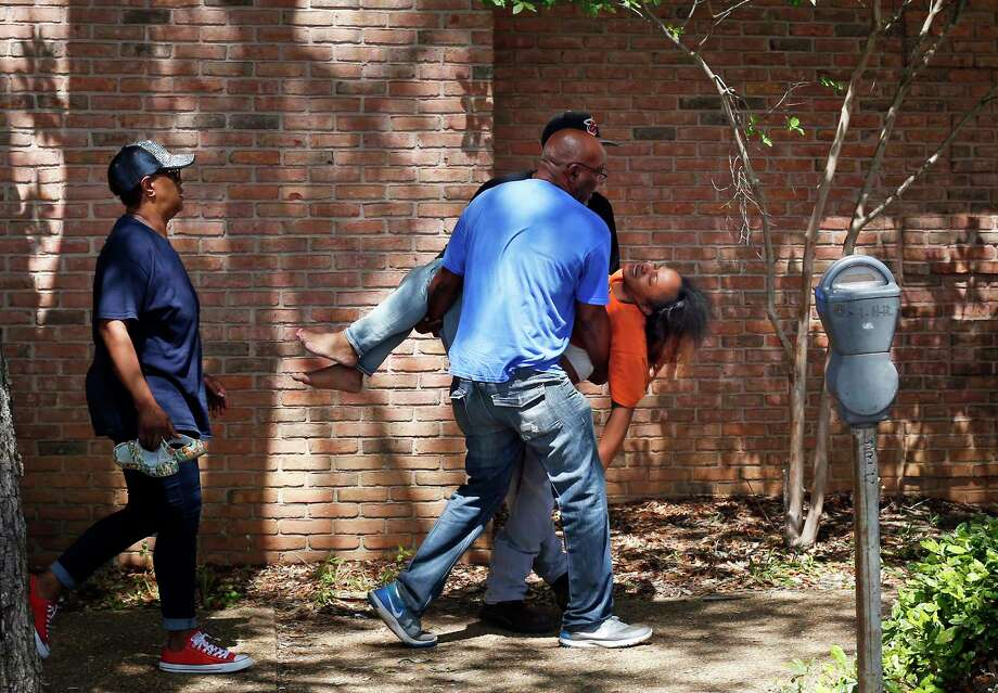 Family members carry a grief-stricken Ebony Archie, mother of Kingston Frazier, after learning the boy was found dead after being kidnapped during the theft of his mother's vehicle Thursday in Jackson, Miss. Photo: Elijah Baylis, MBR / The Clarion-Ledger