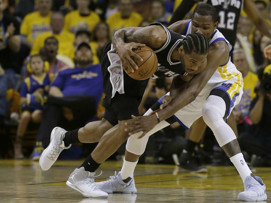 San Antonio Spurs forward Kawhi Leonard, left, dribbles against Golden State Warriors forward Kevin Durant during Game 1 of the NBA basketball Western Conference finals in Oakland, Calif., Sunday, May 14, 2017. (AP Photo/Jeff Chiu) Photo: Jeff Chiu/Associated Press