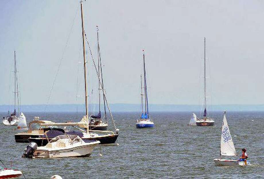 A small sailboat makes its way through other boats moored in Greenwich Harbor, off the coast of Greenwich. The town continues work on a Harbor Management Plan. Photo: File Photo / File Photo / Greenwich Time File Photo