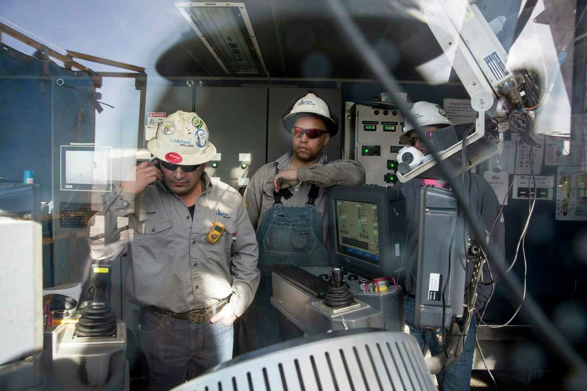 Driller Cristo Flores, left, and Michael Manga, a rig manager, address a drill issue on a Latshaw Drilling rig earlier this year near Midland. Rig counts are rising in Texas.