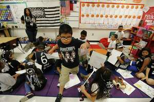 "Roy Cisneros Elementary first grade students in Ms. Jessica Vidaurri's class root for the San Antonio Spurs on Friday, May 19, 2017. Vidaurri - a season ticket holder - has decorated her classroom with Spurs posters, a flag and even a ""shrine"" to honor the team. Her students have written essays about the team and routinely before games will have pep rallies in the classroom. (Kin Man Hui/San Antonio Express-News)"