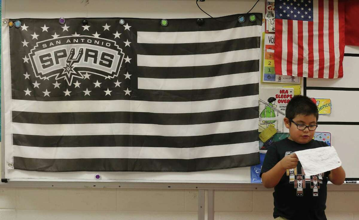 Roy Cisneros Elementary first grade student Trevor Ruiz reads an essay about the Spurs as Ms. Jessica Vidaurri's class roots for the team on Friday, May 19, 2017. Vidaurri - a season ticket holder - has decorated her classroom with Spurs posters, a flag and even a