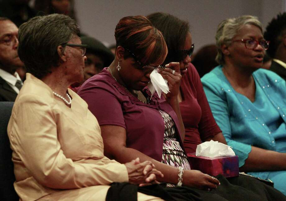 April Mitchell, second from the left, is comforted by family and friends at a memorial for her children, Kyle, 5, Kaila, 6, and Terrance, 13, Friday at City Cathedral Church in The Woodlands. The three died in a fire on May 12 at their family home in Tamina. Photo: Jason Fochtman, Staff Photographer / Conroe Courier / HCN