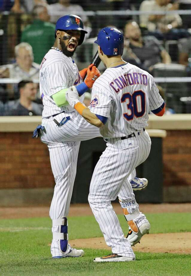 New York Mets' Jose Reyes, left, celebrates with Michael Conforto (30) after Conforto hit a home run during the seventh inning of a baseball game against the Los Angeles Angels Friday, May 19, 2017, in New York. (AP Photo/Frank Franklin II) ORG XMIT: NYM113 Photo: Frank Franklin II / Copyright 2017 The Associated Press. All rights reserved.