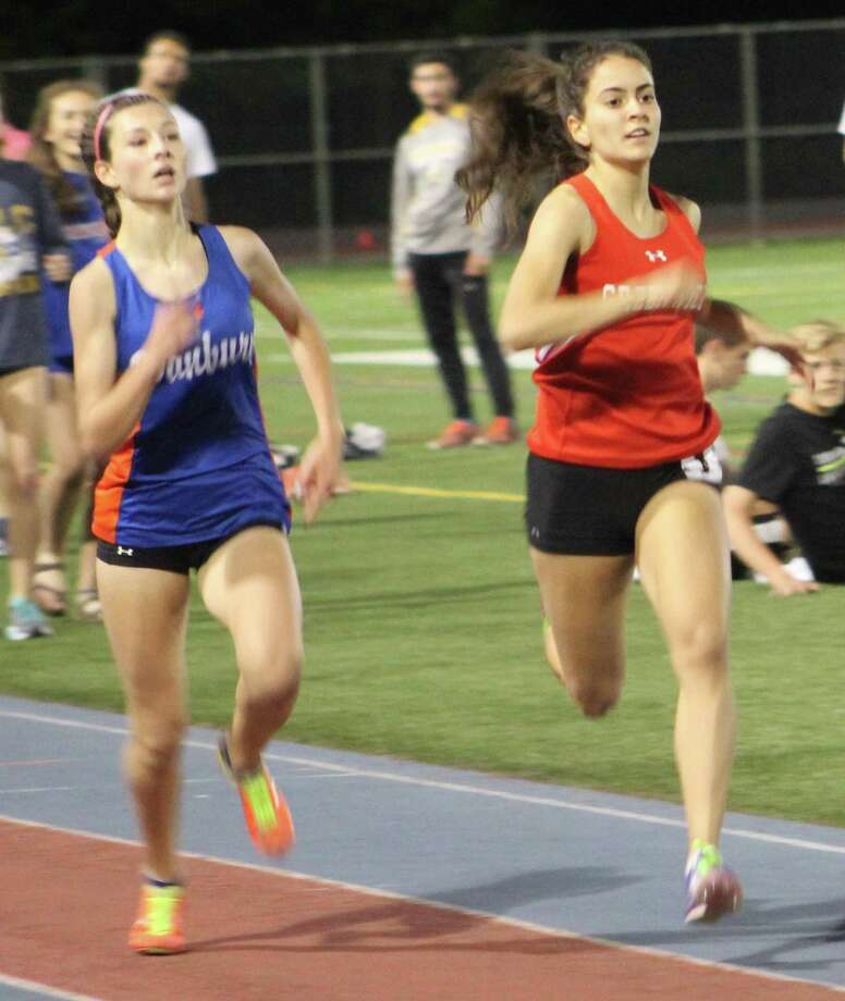 Emily Philippides of Greenwich, right, and Lauren Moore of Danbury sprint to the finish line in the girls one-mile run at the Danbury Dream Invitational track and field meet at Danbury High School May 19, 2017. Philippides won in 5:09.74, while Moore placed second in 5:09.72. Photo: Richard Gregory / Richard Gregory