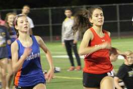 Emily Philippides of Greenwich, right, and Lauren Moore of Danbury sprint to the finish line in the girls one-mile run at the Danbury Dream Invitational track and field meet at Danbury High School May 19, 2017. Philippides won in 5:09.74, while Moore placed second in 5:09.72.