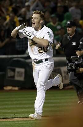 Oakland Athletics' Mark Canha celebrates as he approaches home plate after a solo walk-off home run during the 10th inning of a baseball game against the Boston Red Sox on Friday, May 19, 2017, in Oakland, Calif. (AP Photo/Marcio Jose Sanchez)