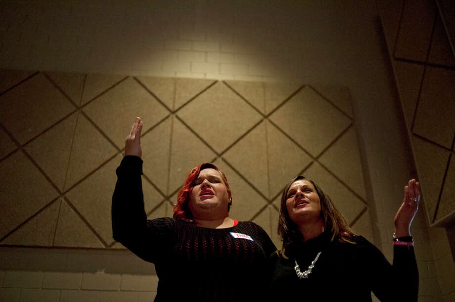 NICK KING | nking@mdn.net  Erica Hansen, right, sings with friend Tara Toma during a Restoration Fellowship service on Jan 9, 2016 at Messiah Lutheran Church in Midland. Hansen is a regular at the Saturday evening service which focuses on healing peoples habits, hangups and hurts. / Midland Daily News