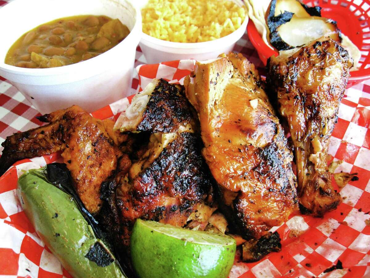A medio pollo plate with half a grilled chicken, onions, a jalapeño, rice, tortillas and an optional side of charro beans from Pollos Asados Los Norteños.