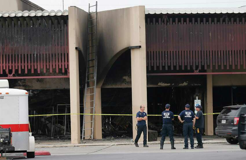 Fire investigators remain at the scene of a four-alarm fire that took the life of SAFD firefighter Scott Deem. On Saturday, May 20, 2017, the scene at the Ingram Square retail center was still heavily blocked off as investigators examine remnants of a structure fire so intense that it resulted in the death of the six-year veteran of the fire department. A few mourners came to pray at a small memorial built near the scene.