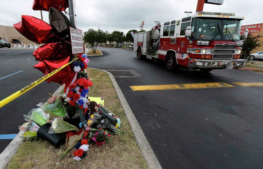 A fire truck from Station 45 passes a memorial at the scene of a four-alarm fire that took the life of SAFD firefighter Scott Deem. On Saturday, May 20, 2017, the scene at the Ingram Square retail center was still heavily blocked off as investigators examine remnants of a structure fire so intense that it resulted in the death of the six-year veteran of the fire department. A few mourners came to pray at a small memorial built near the scene.