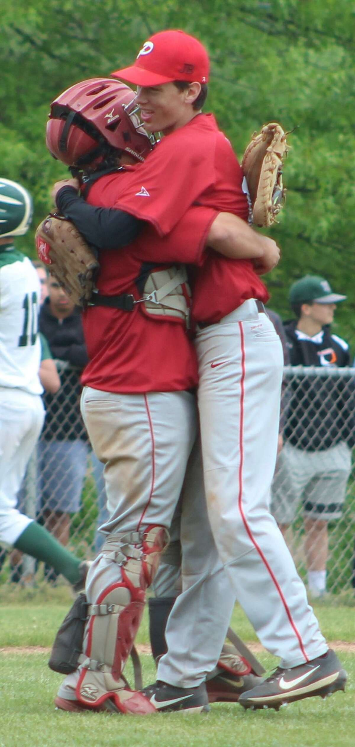 Pomperaug pitcher Ryan Dunfee, right, and catcher Nick Hebert embrace at the conclusion of the Panthers' victory over New Milford in the quarterfinals of the South-West Conference baseball tournament at New Milford High School May 20, 2017.