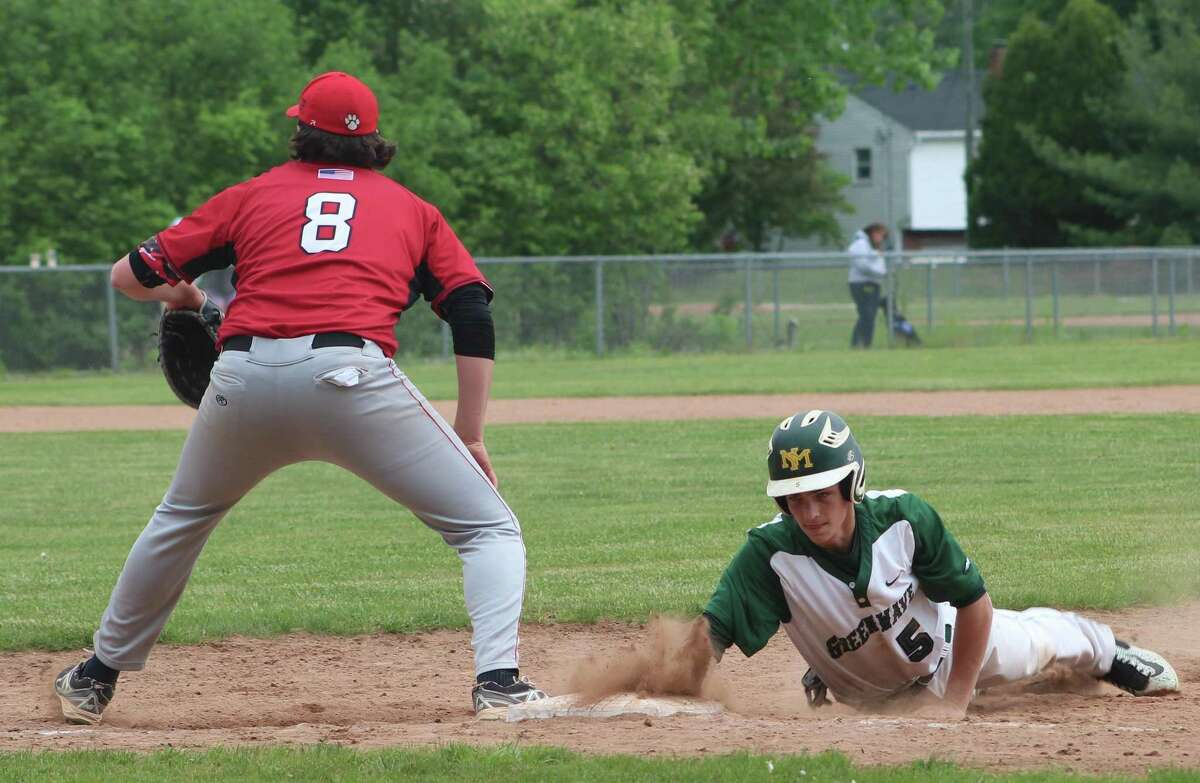 New Milford's Zachary Prahach, right, dives safely back to first base as Pomperaug's Will McDonald awaits the a pick-off throw during the South-West Conference baseball quarterfinal game at New Milford High School May 20, 2017.