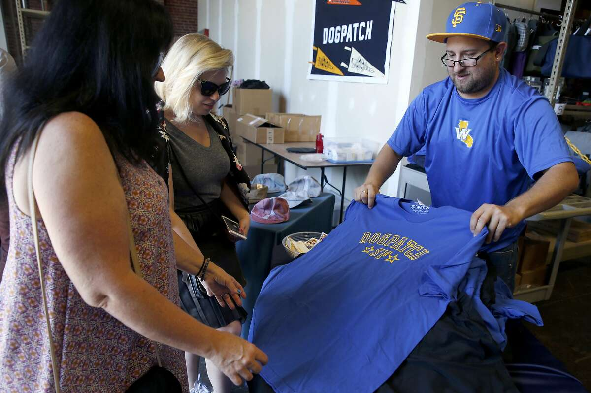 Carlos Godinez sells shirts displaying community pride to JoAnn Barrett (left) and her daughter-in-law Loni Venti at Rickshaw Bagworks during a Dogpatch neighborhood block party in San Francisco, Calif. on Saturday, May 20, 2017.