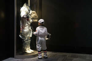 Max Pekarskiy, 4, stands in his space suit as he checks out an Apollo space suit at the opening of the Museum of Flight's new APOLLO exhibit on Saturday, May 20, 2017.