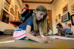Lola McClary, 7, colors during the free family art day at Art Museum of Southeast Texas on Saturday.  Photo taken Saturday 5/20/17 Ryan Pelham/The Enterprise