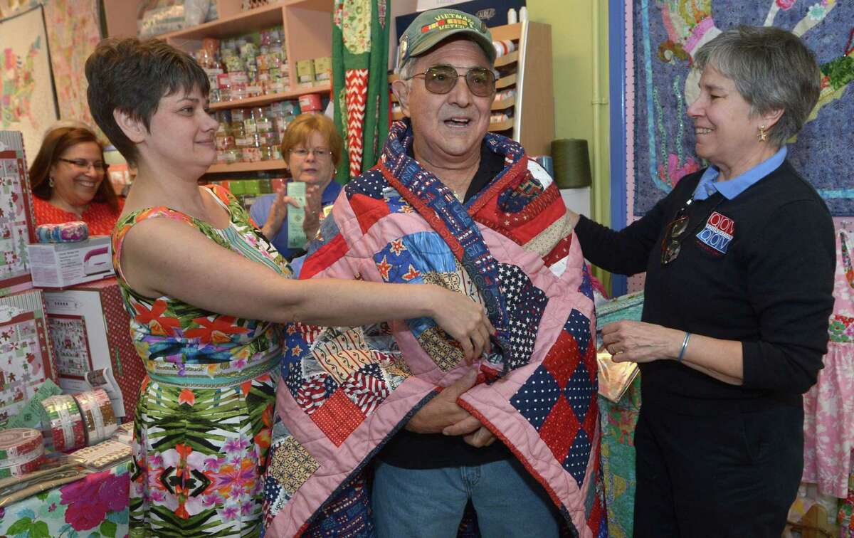 Army veteran James Patchen receives his quilt from Christie Ruiz and Quilts of Valor Connecticut co-coordinator Jane Dougherty during a Quilts of Valor presentation Saturday, May 20, at Christie's Quilting Boutique in Norwalk. Christie's has been one of only three stores in Connecticut and the only one in Fairfield Country to make quilts for Quilts of Valor yet the quilting store has been unable to raise additional funds for the cause and as a result will not be presenting anymore quilts for the project.