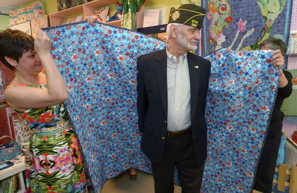 Army veteran Robert Tirreno receives his quilt from Christie Ruiz and Quilts of Valor Connecticut co-coordinator Jane Dougherty during a Quilts of Valor presentation Saturday, May 20, at Christie's Quilting Boutique in Norwalk. Christie's has been one of only three stores in Connecticut and the only one in Fairfield Country to make quilts for Quilts of Valor yet the quilting store has been unable to raise additional funds for the cause and as a result will not be presenting anymore quilts for the project.