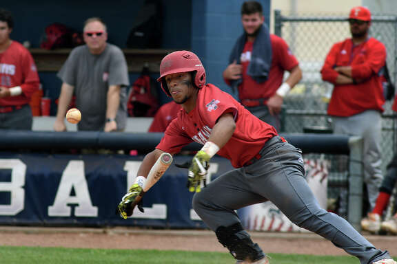 Fort Bend Travis senior outfielder Nathan Armstead lays down a bunt which he turned into a single during the Tiger's 7-run top half of the 6th inning of the final game of their best of 3 Class 6A Region III Regional Quarterfinal Baseball Playoff series versus Katy at Tompkins High School on Saturday, May 20, 2017. (Photo by Jerry Baker/Freelance)