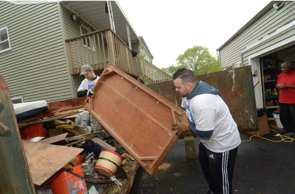 Bankwell employees Alex Sparadafora and Sebastian Giraldo join a contingent from Wilton Kiwanis and Club volunteering to clean and repair the house of Janet Mosely at 91 Bouton St. as 1,800 local residents kick off this year's campaign to revitalize 60 homes for low-income Connecticut families, beginning with the 30th annual HomeFront Day on Saturday, May 6, in Norwalk.