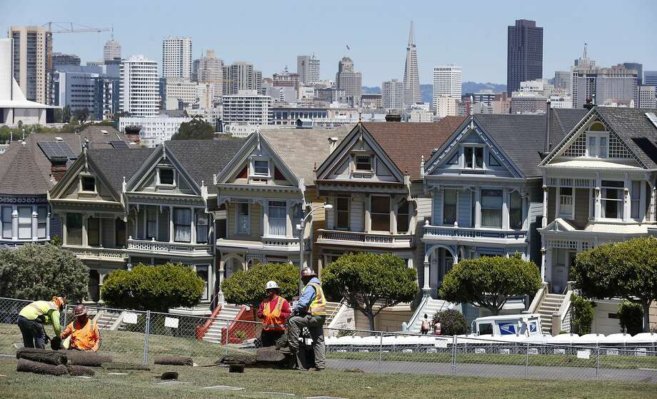With the iconic Painted Ladies as a backdrop, a crew finishes landscaping renovations at Alamo Square Park. Photo: Paul Chinn, The Chronicle