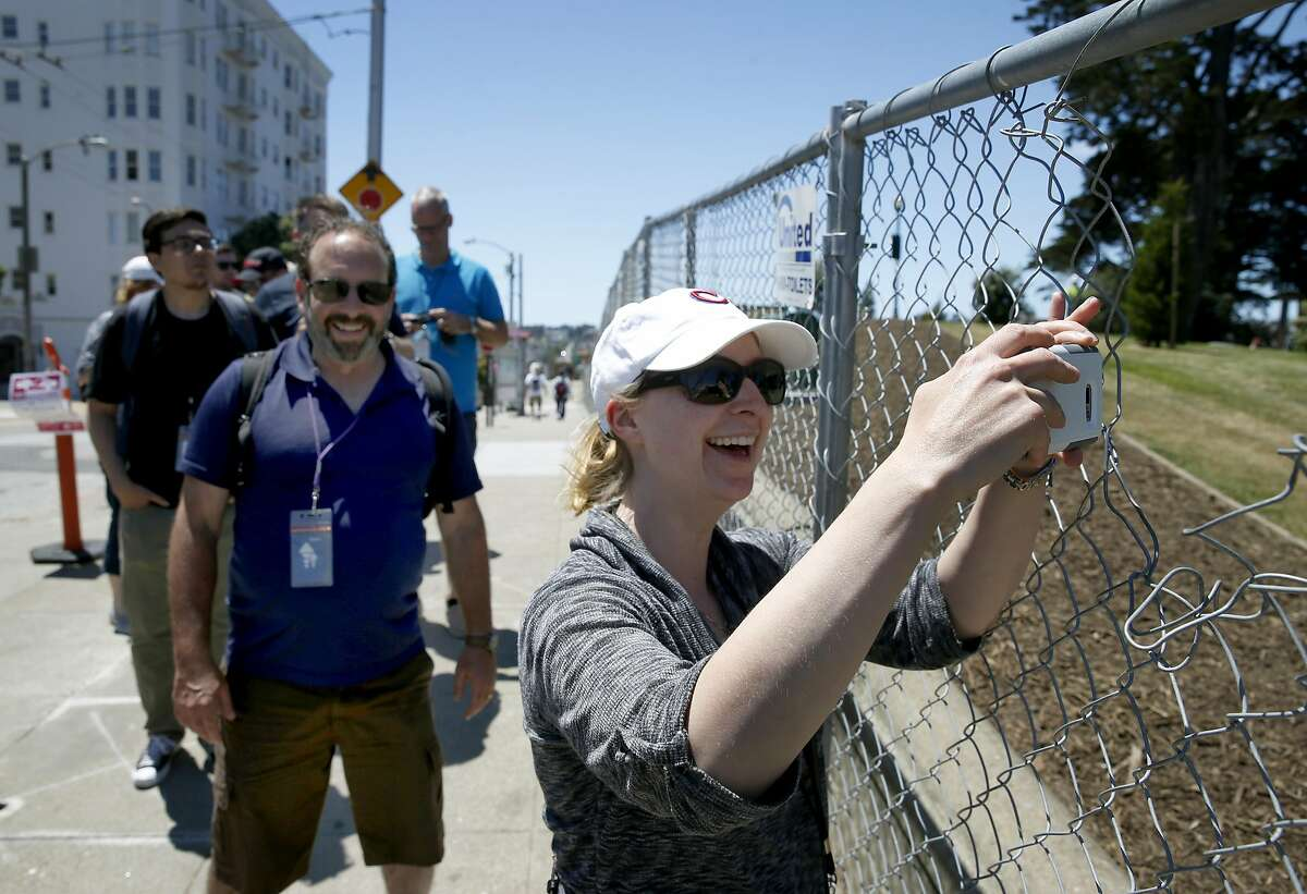 Visiting from Canada, Amanda Craig snaps a photo of the iconic Painted Ladies row of houses through an opening in a construction fence surrounding Alamo Square Park while on a guided tour led by Chris Courtney (left) in San Francisco, Calif. on Saturday, May 20, 2017. The park is slated to reopen to the public Wednesday after an extensive makeover.