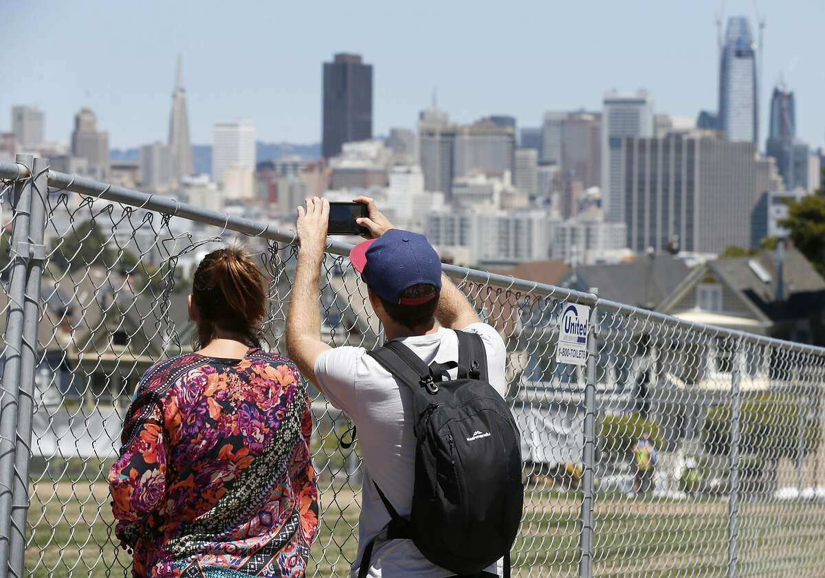Visitors try to capture a photograph of the iconic Painted Ladies row of houses from behind a construction fence surrounding Alamo Square Park in San Francisco, Calif. on Saturday, May 20, 2017. The park is slated to reopen to the public Wednesday after an extensive makeover.