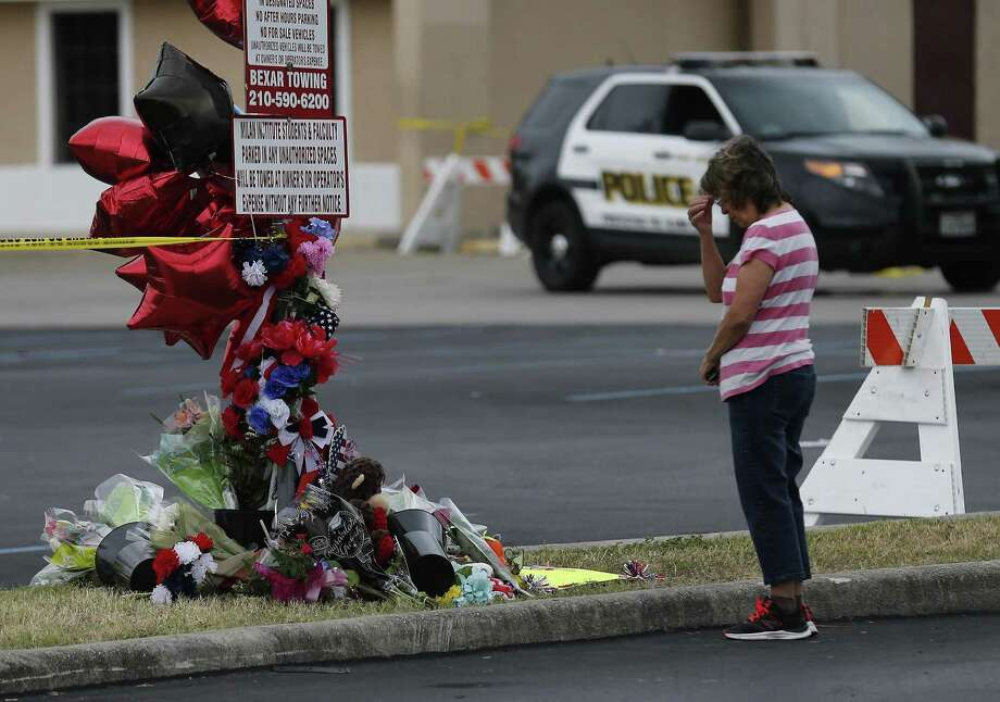 A mourner prays near a memorial as fire investigators remain at the scene of a four-alarm fire that took the life of SAFD firefighter Scott Deem. On Saturday, May 20, 2017, the scene at the Ingram Square retail center was still heavily blocked off as investigators examine remnants of a structure fire so intense that it resulted in the death of the six-year veteran of the fire department. A few mourners came to pray at a small memorial built near the scene. (Kin Man Hui/San Antonio Express-News) Photo: Kin Man Hui, Staff / San Antonio Express-News / ©2017 San Antonio Express-News