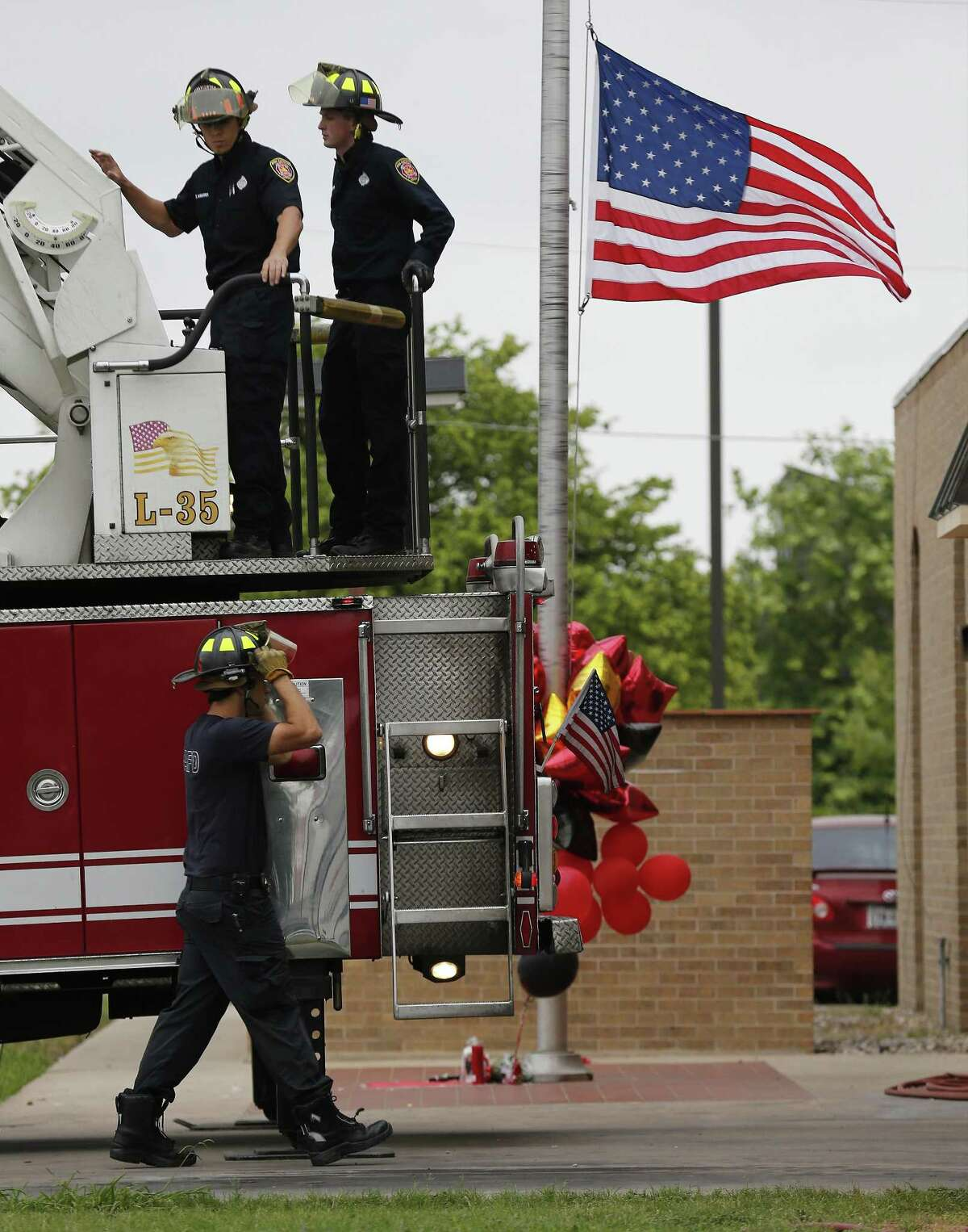 Firefighters at Fire Station No. 35 carry on with their work as the station's flag is flown at half mast on Saturday, May 20, 2017. Fire investigators remain at the scene of a four-alarm fire that took the life of SAFD firefighter Scott Deem. The scene at the Ingram Square retail center was still heavily blocked off as investigators examine remnants of a structure fire so intense that it resulted in the death of the six-year veteran of the fire department. A few mourners came to pray at a small memorial built near the scene. (Kin Man Hui/San Antonio Express-News)
