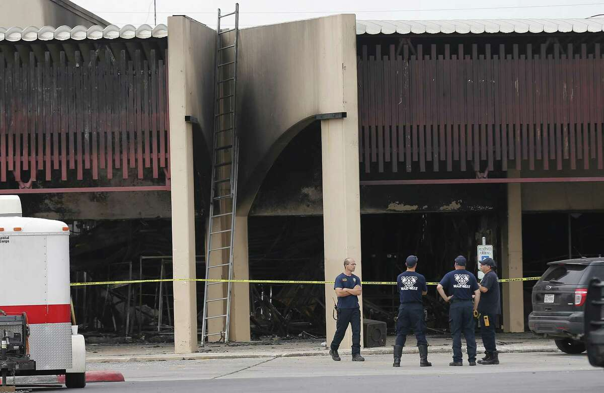 Fire investigators remain at the scene of a four-alarm fire that took the life of SAFD firefighter Scott Deem. On Saturday, May 20, 2017, the scene at the Ingram Square retail center was still heavily blocked off as investigators examine remnants of a structure fire so intense that it resulted in the death of the six-year veteran of the fire department. A few mourners came to pray at a small memorial built near the scene. (Kin Man Hui/San Antonio Express-News)