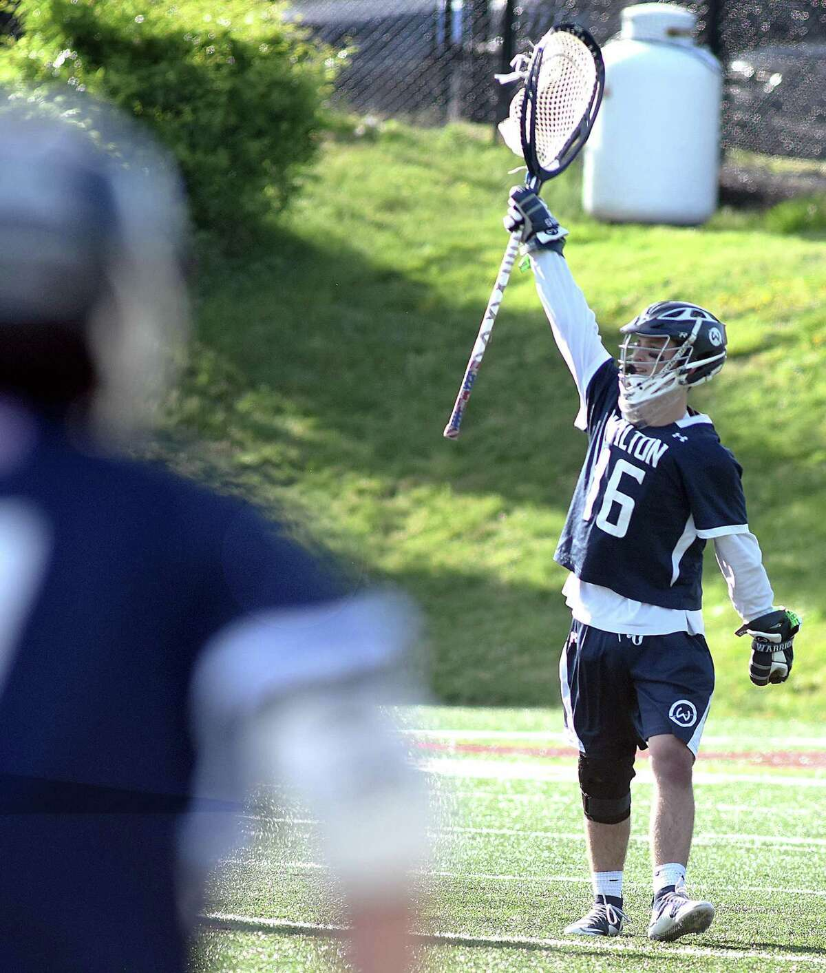 Wilton goalie Andrew Calabrese hoists his stick in victory after the final buzzer in the Warriors 9-7 FCIAC boys lacrose quarterfinal win over New Canaan at Dunning Field in New Canaan. Calabrese made 12 saves to backstop the Wilton win.
