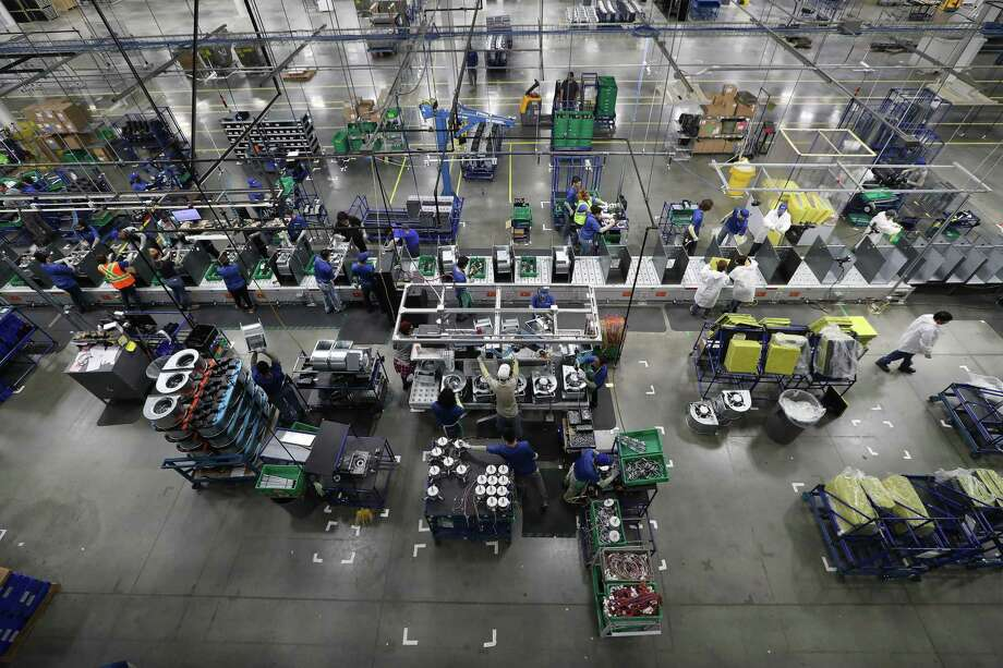 """Workers assemble air conditioning units in the new Daikin facility Wednesday, May 10, 2017, in Waller before it officially opens on May 24. It is the world's largest  building of this particular construction type (called """"tilt-wall""""). It's four million square feet, about the size of 40 city blocks, or 91 acres. The plant bring several thousand manufacturing jobs to Houston when it opens. They make air conditioning, heating and ventilation units. ( Steve Gonzales  / Houston Chronicle ) Photo: Steve Gonzales, Staff / © 2017 Houston Chronicle"""