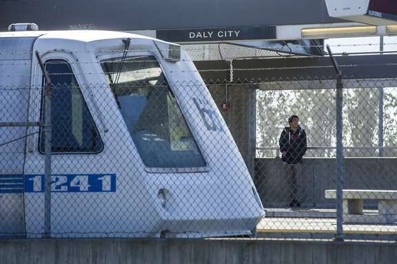 A man waits for a BART train on Saturday, May 20, 2017, in Daly City, Calif. The train seen is halted at the Daly City BART Station as officials work on removing a derailed train.  Two cars in a nine-car BART train derailed at approximately 3 p.m. between the Daly City and Balboa Park BART stations forcing the evacuation a couple dozen passengers and causing major delays.