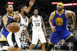 San Antonio Spurs' Patty Mills looks for room around Golden State Warriors' Stephen Curry and JaVale McGee during first half action in Game 3 of the Western Conference Finals held Saturday May 20, 2017 at the AT&T Center.
