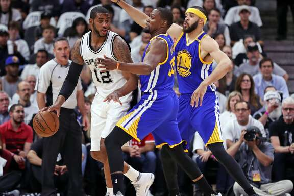 Golden State Warriors' Kevin Durant and JaVale McGee guard San Antonio Spurs' LaMarcus Aldridge in 1st quarter during Game 3 of NBA Western Conference Finals at AT&T Center in San Antonio, Texas, on Saturday, May 20, 2017.