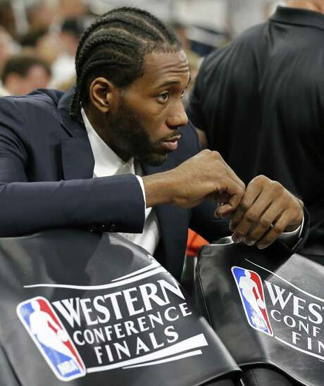 Kawhi Leonard, who was held out of Game 3 on Saturday, sits behind the bench and watches. Leonard has been out since the second half of Game 1. Photo: Edward A. Ornelas /San Antonio Express-News / © 2017 San Antonio Express-News