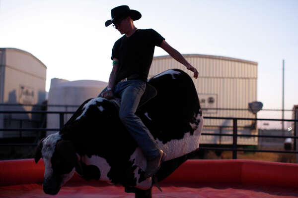 A concert attendee rides a mechanical bull during the Crudefest country music festival May 20, 2017. James Durbin/Reporter-Telegram