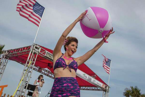 Charissa Wylie shows a beachball to the crowd while competing in the Galveston Island Beach Revue Bathing Beauties Contest at the Hotel Galvez and Spa in Galveston, Texas, Saturday, May 20, 2017. Contestants donned vintage swimwear for the event which official signals the start of summer on the island. (Stuart Villanueva/The Galveston County Daily News via AP)