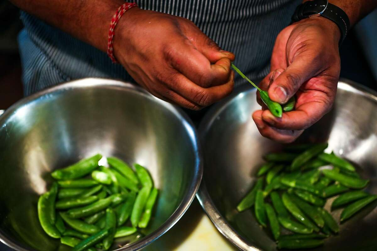 Chef Rupam Bhagat cleans sugar snap peas for a salad at Dum Indian Restaurant in San Francisco, California, on Monday, May 8, 2017.