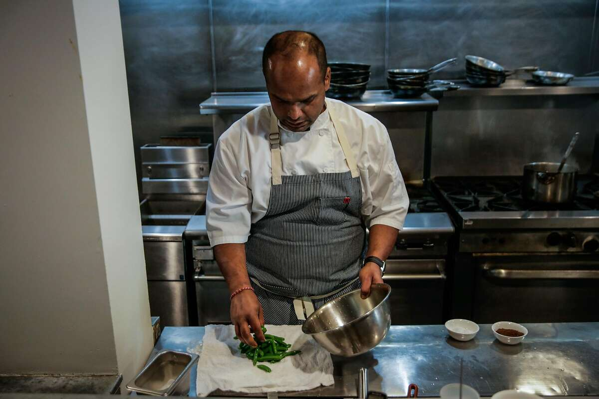 Chef Rupam Bhagat removes sugar snap peas from ice after blanching them while preparing the sugar snap pea salad at Dum Indian Restaurant in San Francisco, California, on Monday, May 8, 2017.