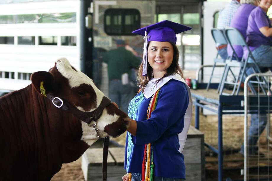 Emaline Robinson wore her graduation cap in the arena Saturday morning at the auction. The senior hoped to raise money for scholarships for college. Photo: David Taylor