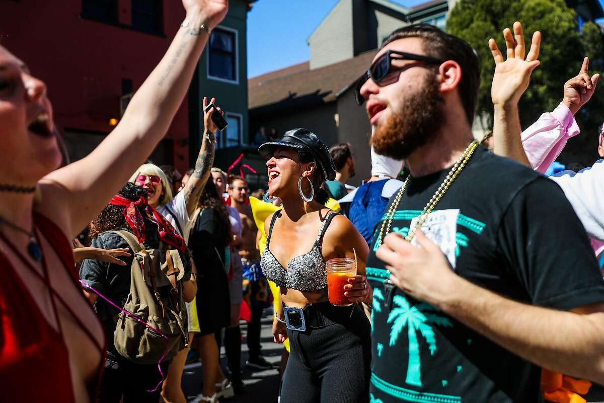 Laura C. (center) dances on Fell Street during the Bay to Breakers annual race in San Francisco, California, on Sunday, May 21, 2017.