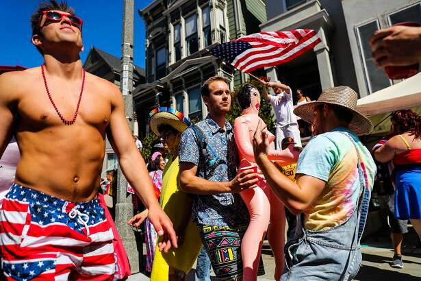 Henry S. (center) dances with a plastic doll on Fell Street during the Bay to Breakers annual race in San Francisco, California, on Sunday, May 21, 2017.