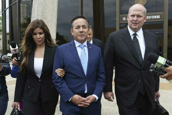 State Sen. Carlos Uresti, center, leaves the San Antonio federal courthouse Wednesday after making an initial appearance in his criminal case. With Uresti are his wife, Lleanna, and attorney Mikal Watts. U.S. prosecutors may try to remove Watts from the case.