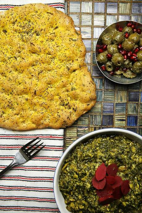 Kolaas bread (clockwise from top left), fava beans and herb stew, and marinated olives and pomegranate seeds made by Hanif Sadr in Berkeley. Photo: Santiago Mejia, The Chronicle