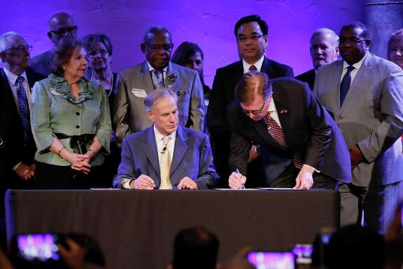Lt. Governor Dan Patrick signs the bill as Governor Greg Abbott looks on during the SB 24 signing ceremony during the 11:00 am worship service at Grace Church, The Woodlands on Sunday, May 21, 2017.