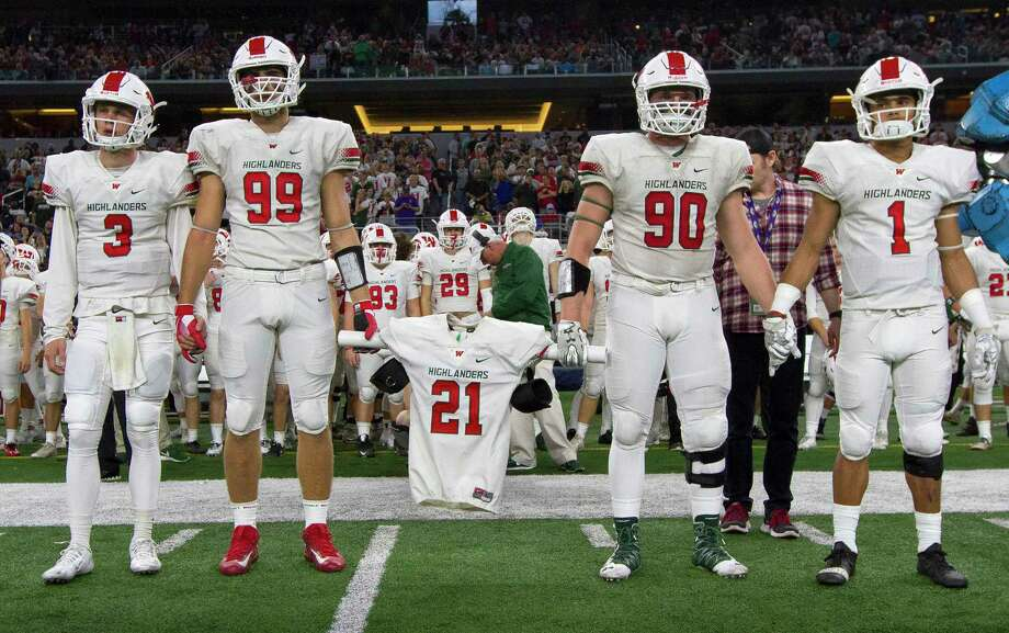 The Woodlands football players Michael Purcell, left, and Zachary Loane carry the jersey of linebacker Grant Milton, who was named an honorary captain before a UIL Class 6A Division I state final against Lake Travis at AT&T Stadium Saturday, Dec. 17, 2016, in Arlington. Photo: Jason Fochtman, Staff Photographer / Houston Chronicle