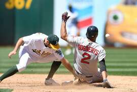 OAKLAND, CA - MAY 21:  Xander Bogaerts #2 of the Boston Red Sox steals second base, beating the throw to Adam Rosales #16 of the Oakland Athletics in the top of the fifth inning at Oakland Alameda Coliseum on May 21, 2017 in Oakland, California.  (Photo by Thearon W. Henderson/Getty Images)