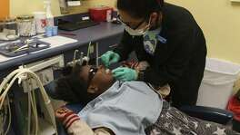 Ruby Ayala prepares Kourtnee Thomas, 8, for an extraction during a free dental clinic at Kool Smiles General Dentistry for Kids, Sunday, May 21, 2017. The services were provided as part of the annual Sharing Smiles Day, offering uninsured and underinsured kids up to 18 free dental exams, extractions, restorative care and emergency care.