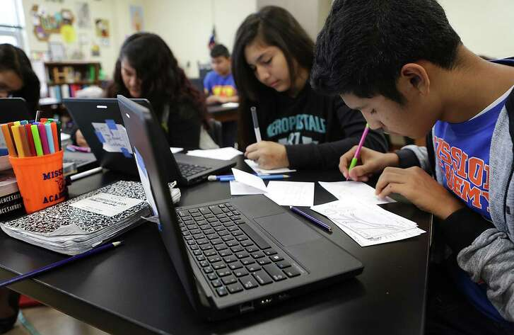 Gabriel Gonzalez, right, and Faith Guzman, center, work on a semester review in eight grade science at SAISD's Mission Academy.  The school has been rated highly by the Children at Risk school ranking.